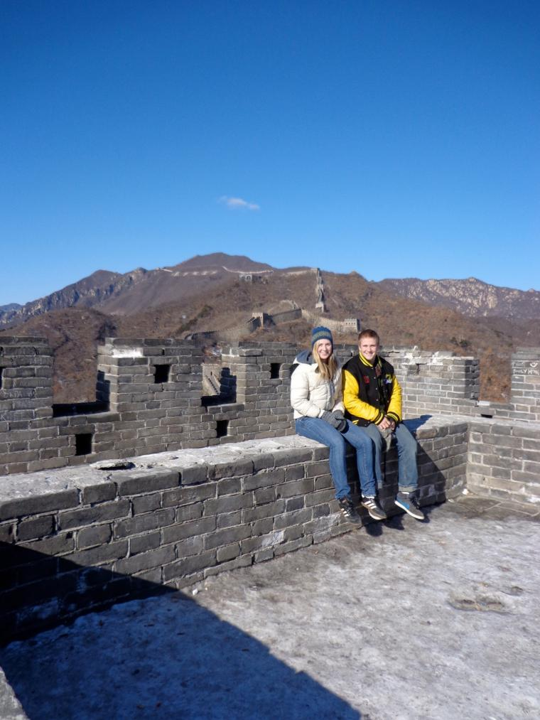 Photograph of a man and a woman smiling while posing by the Great Wall of China.