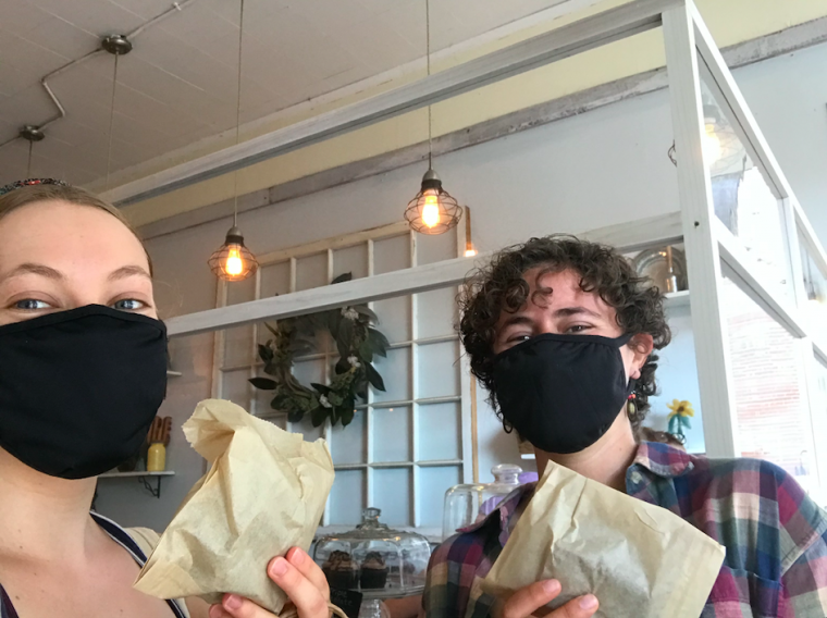 Ruth and Piper wearing masks, holding brownies in the local bakery