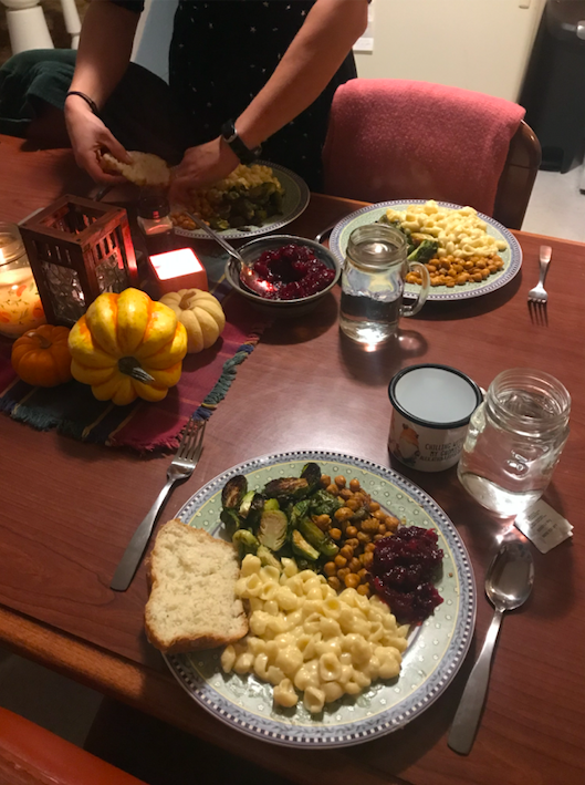 Thanksgiving table with plates of food, candles, and mini decorative pumpkins