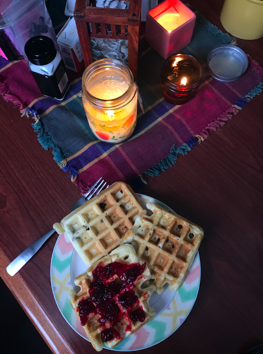 dining table with waffles and candles on it