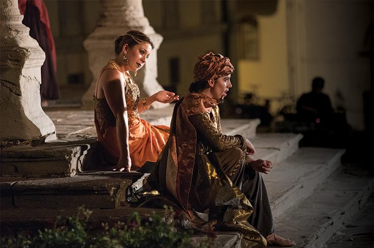 Seated on stone steps, two people perform a scene in costume