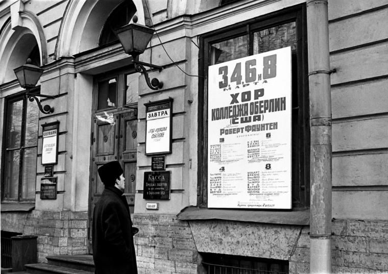 Black and white photo of a man looking at a poster written in Russian