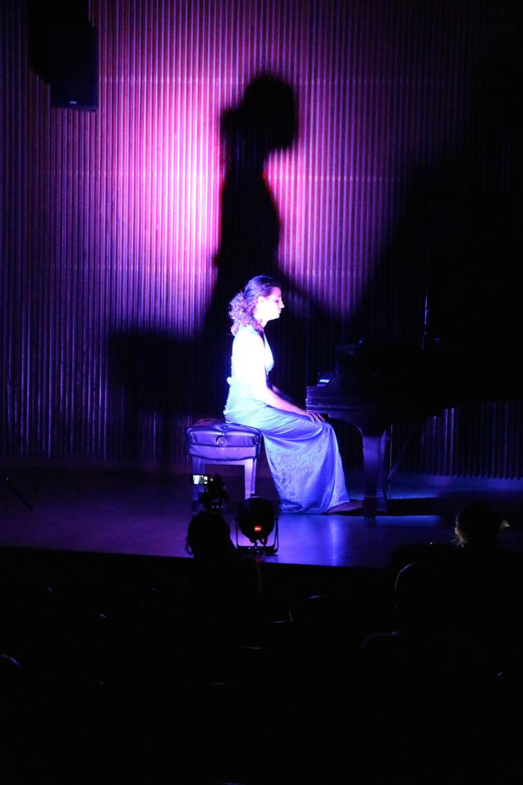 A woman seated at a piano on stage