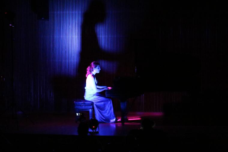 A woman plays a piano on stage