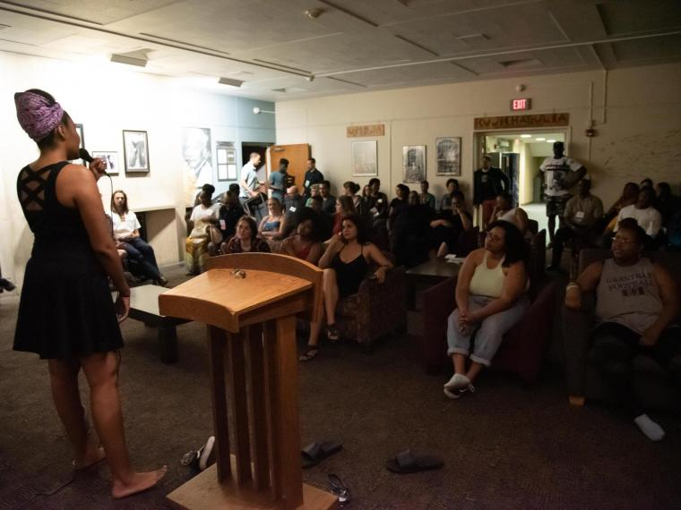 student participates in a soul session in front of a crowd at Afrikan Heritage House.