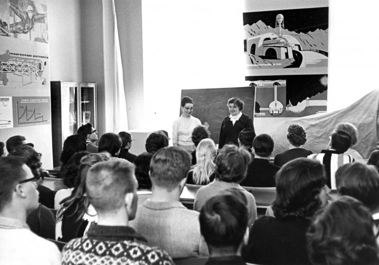 Black and white photo of two people standing in front of an audience with charts and diagrams on the walls