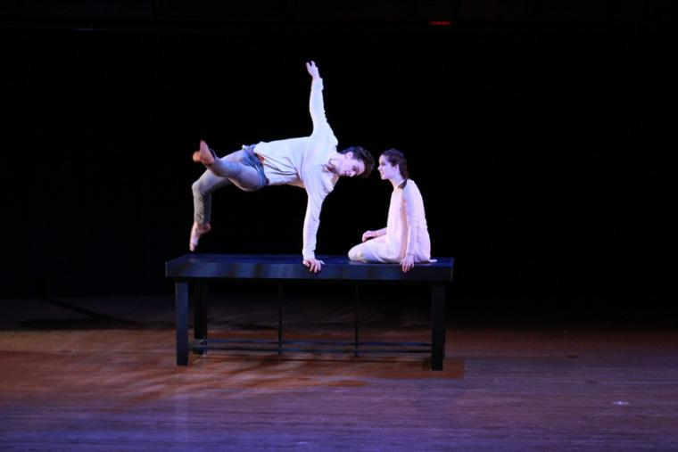 Two people perform a dance routine atop a table