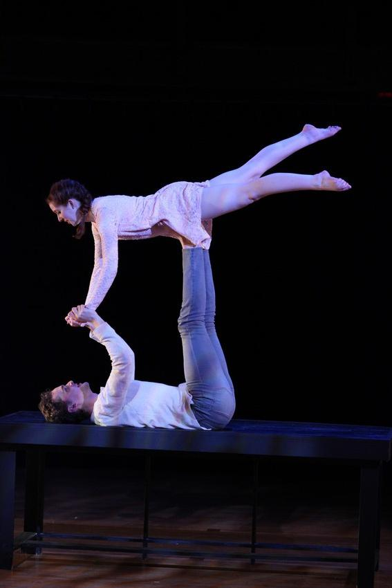 A man lies on his back as he hoists a woman in the air during a dance routine