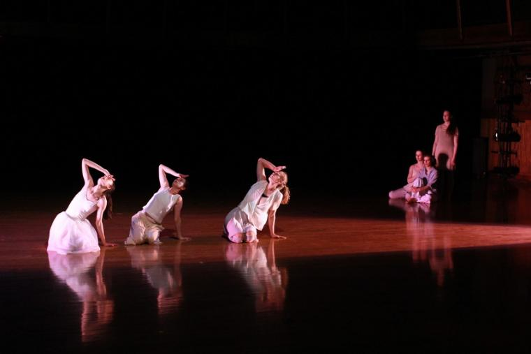 Three dancers hold their hands to their foreheads, as three others look on during a dance routine