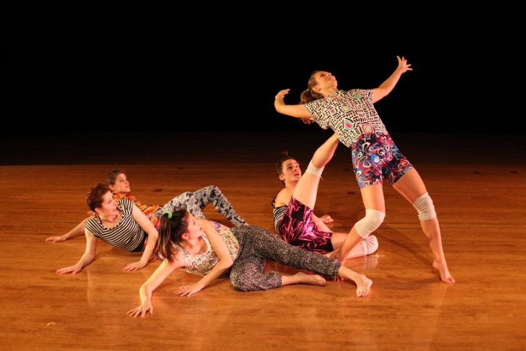 One dancer feigns falling backwards as four others lie on the ground during a dance routine