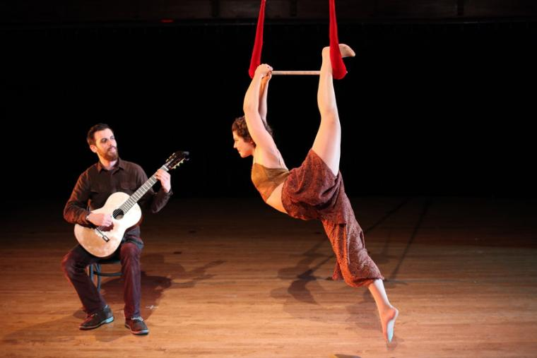 A woman performs a trapeze routine while a man performs guitar