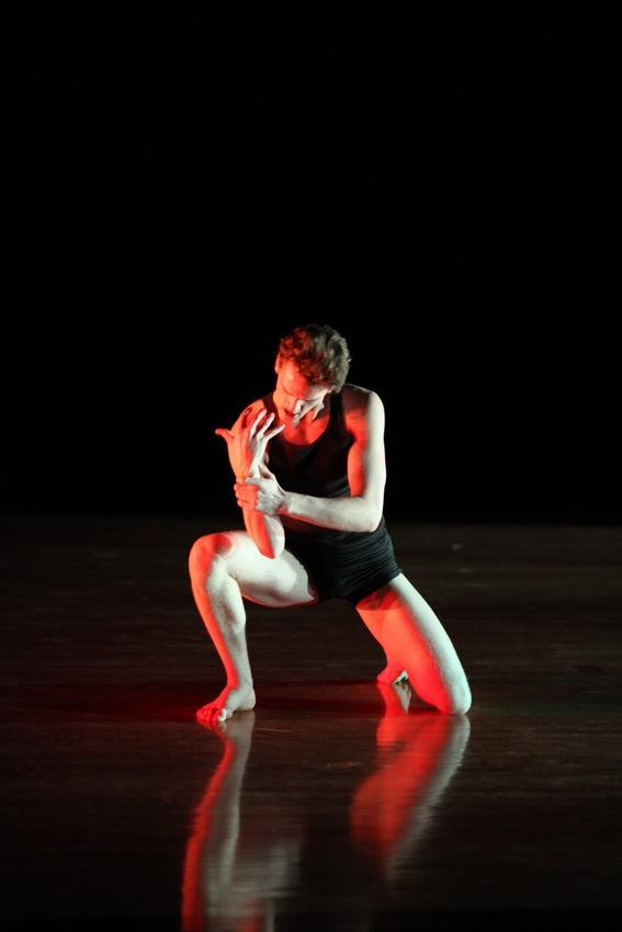 A man crouches down, clutching his wrist during a dance routine