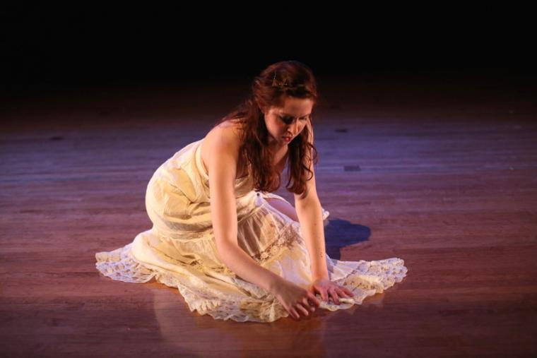 A woman in a white dress kneels on stage
