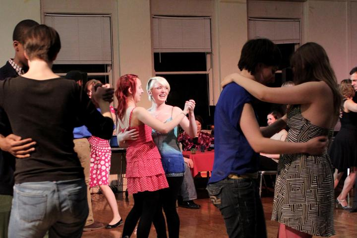 Photograph of people dancing with each other.