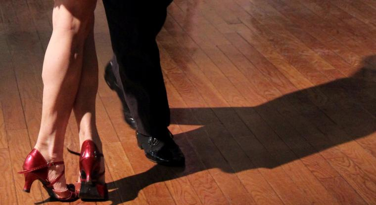 The feet of two dancers. One in heels and one in flat dress shoes.