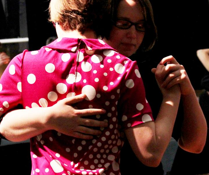 Photograph of two people dancing with each other.