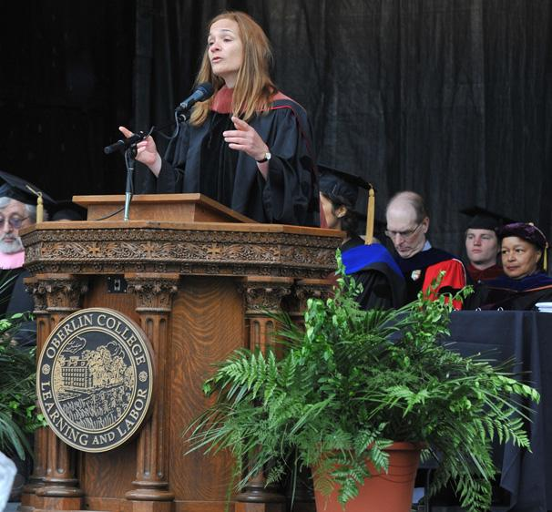 A person in commencement regalia speaks from behind a podium