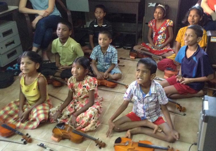 Many children site cross-legged with violins in front of them