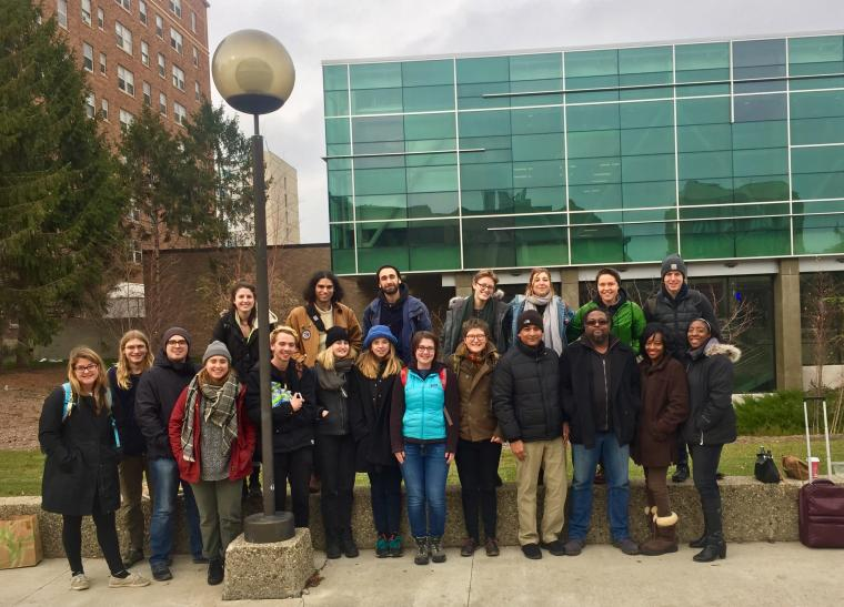 Group photograph of students and faculty in front of a building.