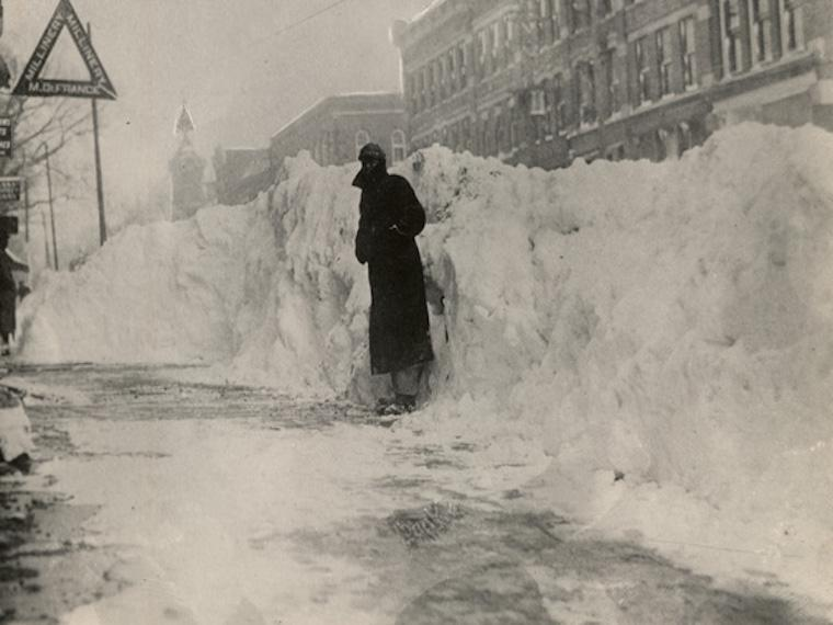 A man standing in front of a snow pile in downtown Oberlin.