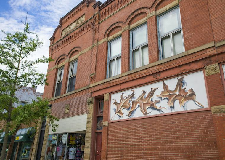 A brick building with a mural of oak leaves on it