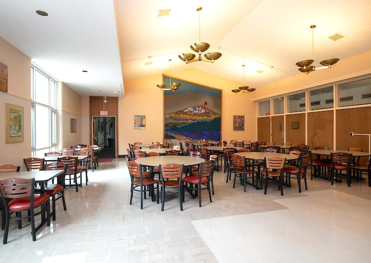 An empty dining hall with a large mural of a mountain on the far wall.