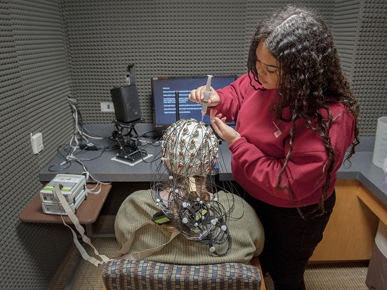 student working in lab with EEG cap.