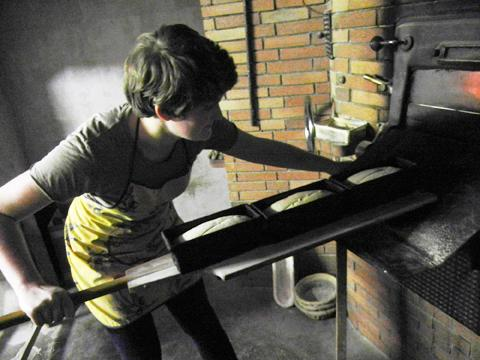 A person placing a plank of bread in a large brick oven
