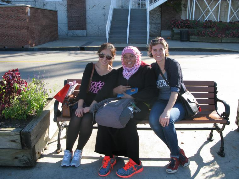 Photograph of three people sitting on a bench.