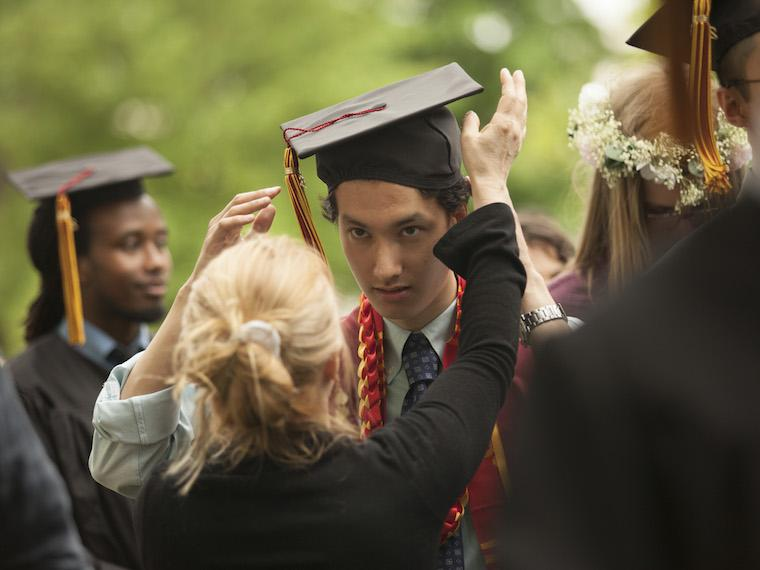 woman adjusts the mortarboard of a student in line for commencement.