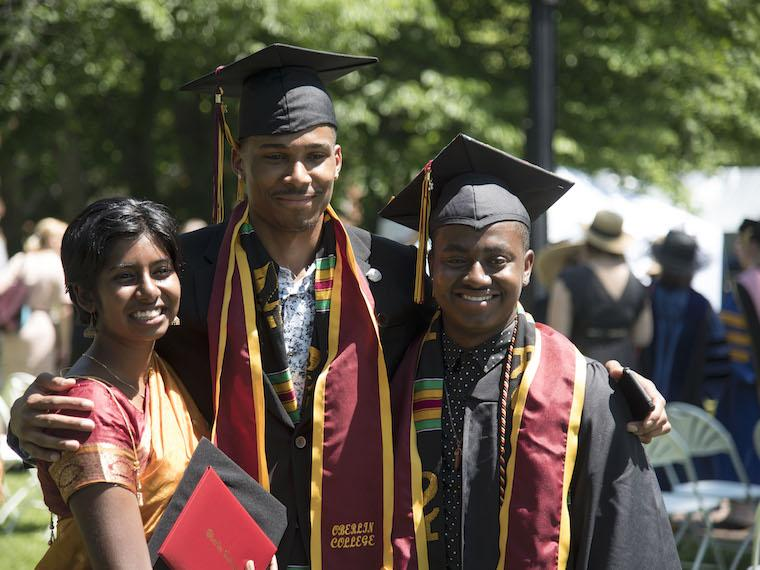 three students, two in cap and gown celebrate commencement.